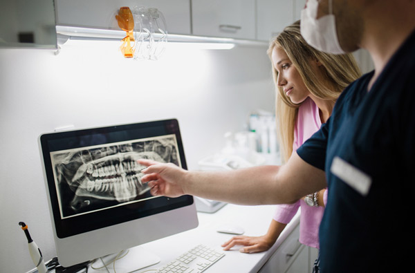 Dentists reviewing dental x-rays on computer monitor